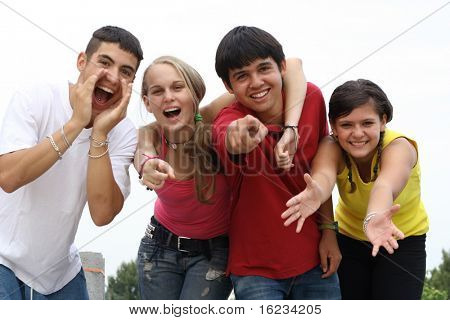 four confident teenagers reaching out
