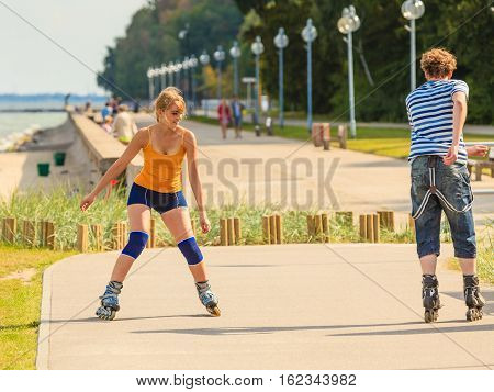 Holidays active people and friendship concept. Young fit couple on roller skates riding outdoors on sea coast woman and man rollerblading together on the promenade