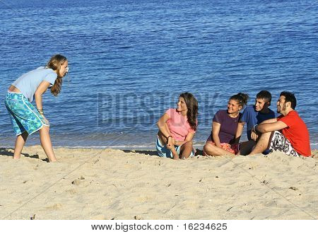 young woman takes photo of her friends on the beach