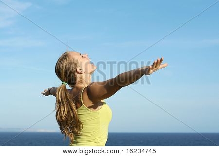 Young girl arms out stretched to the sky. Might be good to advertise travel.