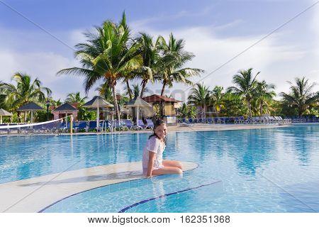 Cayo Coco island, Memories Carib resort, Cuba, June 30, 2016, joyful smiling happy little girl sitting on the edge of swimming pool on early morning at Memories Carib resort