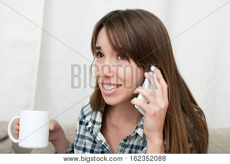Portrait of young woman talking by phone and drinking coffee indoor. Attractive woman talking to someone on her mobile phone and smiling, close up