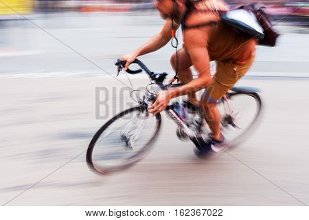 bicycle messenger on the road shown in motion blur