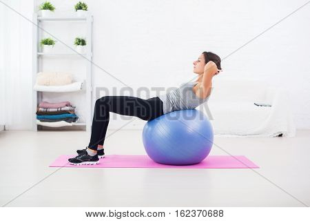 Fitness young woman doing abdominal crunches on fit ball