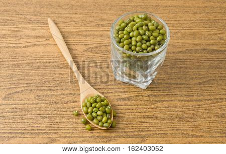Cuisine and Food Raw and Uncooked Mung Dried Beans in A Wooden Spoon and A Tumbler.