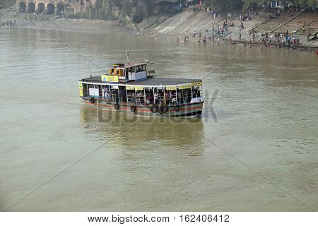 KOLKATA, INDIA - FEBRUARY 10: Ferry boat crosses the Hooghly River nearby the Howrah Bridge in Kolkata on February 10, 2016. To use the ferry is easy, fast and cheap way how to cross the Hooghly River