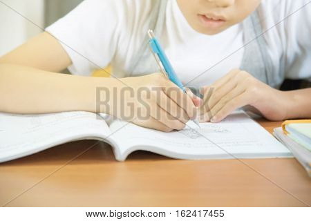 Young student Asian pre teens girl doing homework on wooden table indoors with copy space selective focus on cartoon drawing. Kid pay attention writing on book in house or school education concept.