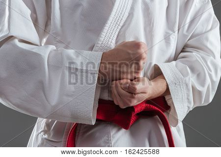Cropped image of sportsman dressed in kimono practice in karate and gesture with hand isolated over grey background.