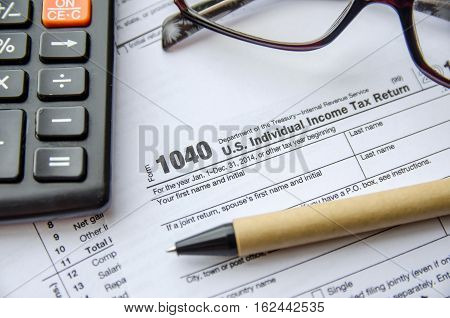 Individual income tax return form glasses pen and calculator