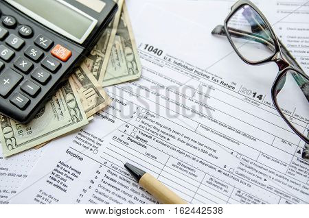 federal income tax return IRS 1040 documents with pen calculator dollars