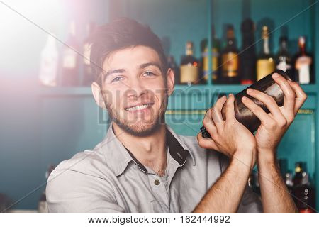 Young handsome smiling barman in bar interior shaking and mixing alcohol cocktail. Professional bartender portrait at work in night club with shaker in hands. Service industry occupation