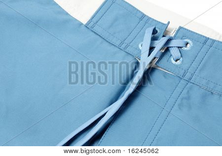 closeup of a blue boardshorts on a white background