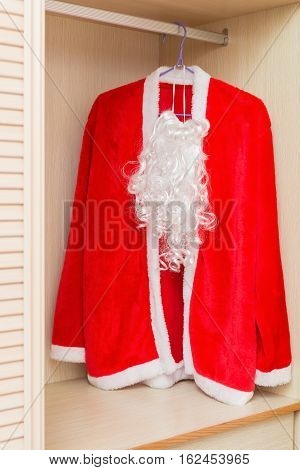 Santa Claus Coat and Beard hanging in a wardrobe