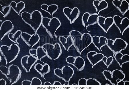 several hearts drawn with a chalk on a blackboard