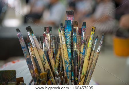 Artist Paintbrushes In Dirty Bucket.