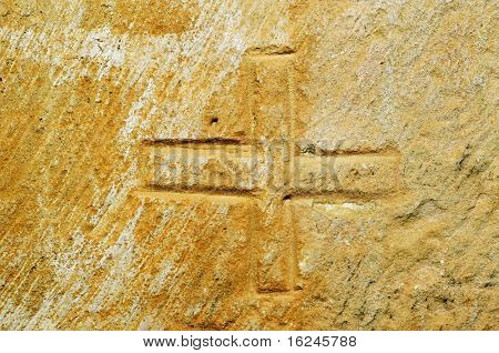 a cross graved on a stone as a mason's mark