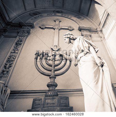Sculpted virgin lighting a seven candlestick in Recoleta cemetery