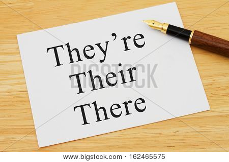 Learning to use proper grammar A white card on a desk with a pen with words They're Their and There