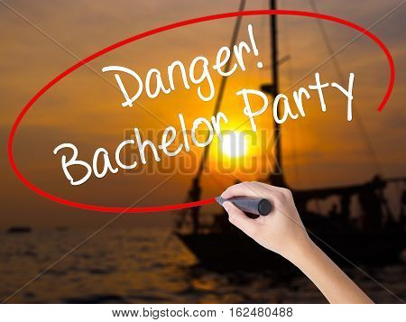 Woman Hand Writing Danger! Bachelor Party With A Marker Over Transparent Board