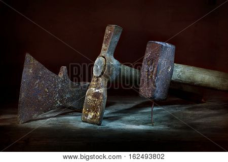 On the wooden table is a group of objects. Rare old carpentry tools. Hammer, chisel, hammer, pickaxe. Tools old, rusty with wooden handles. The photo was taken using a light brush effect it.