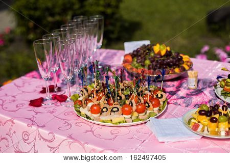 empty glasses stand on a festive table with food preparation for the wedding feast squid shrimp with cheese and tomatoes on toothpicks fruit on the table grapes peaches fruit candy napkins glasses petals