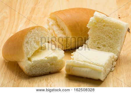 Hotdog bread filled with sweetened butter cream on a wooden board