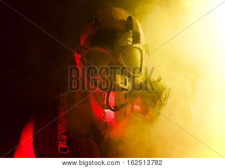 A creepy guy with post apocalyptic vibes wearing a gasmask in a smoke or fog cloud that's colored bright yellow while being lit with a red light from other side.