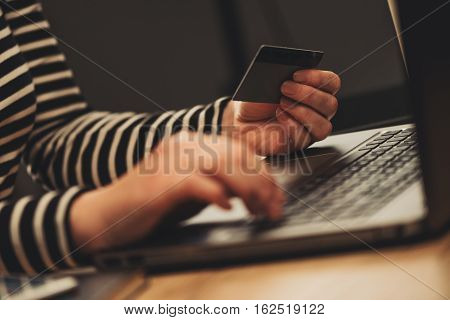 E-commerce concept - woman using laptop and credit card close up of female hands typing e-wallet credentials for an online purchase transaction
