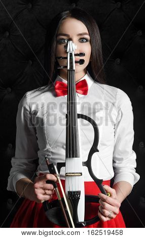 Young woman face with a violin. In white shirt with a bow tie. Hands holding a violin