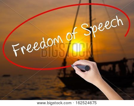 Woman Hand Writing Freedom Of Speech With A Marker Over Transparent Board