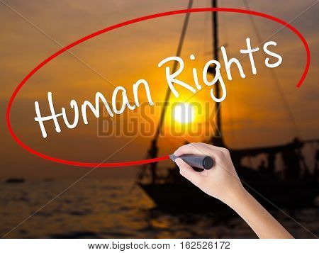 Woman Hand Writing Human Rights With A Marker Over Transparent Board