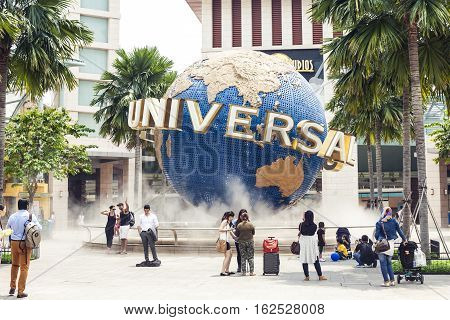 Singapore, Republic of Singapore - 05 november 2014: Tourists and theme park visitors taking pictures of the large rotating globe fountain in front of Universal Studios
