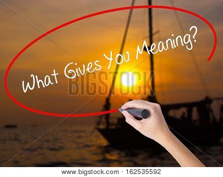 Woman Hand Writing What Gives You Meaning? With A Marker Over Transparent Board