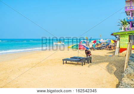HIKKADUWA SRI LANKA - DECEMBER 5 2016: The comfortable sand beach with sun beds umbrellas cafes and restaurants for the tourist pleasure on December 5 in Hikkaduwa.