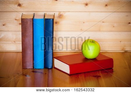 Books and green apple on wooden table over wooden background