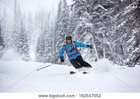 Skier moving very fast in forest. Off-piste slope at ski resort