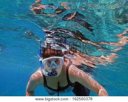 Girl snorkeling underwater in the sea around the island