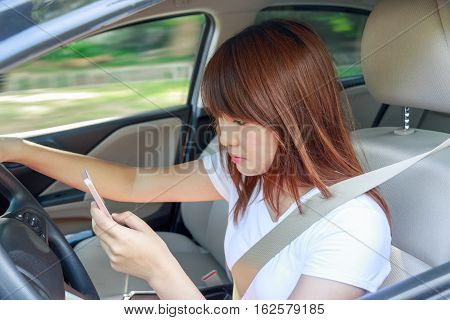 Woman watching video or text to someone with smart phone while driving fast a car distracted.