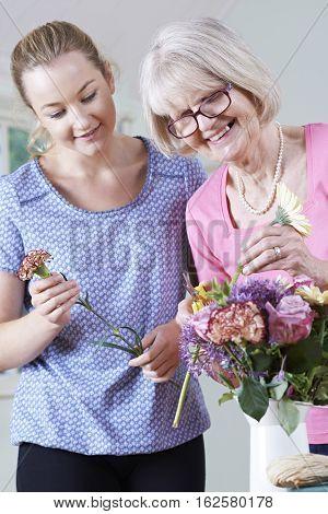 Senior Woman With Teacher In Flower Arranging Class