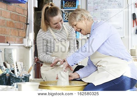 Senior Woman With Teacher In Pottery Class
