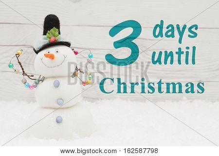 Christmas countdown message Some snow and a snowman on weathered wood with text 3 days until Christmas