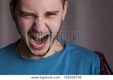 Portrait of a twenty-year-old man in a blue shirt and plaid shirt with natural light with flash on a white background screaming man feelings of anger rage hatred a man in a rage