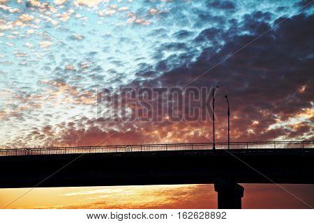 sunset over the bridge the bridge in the sun beautiful yellow-orange clouds over the bridge blue-orange sky over the road