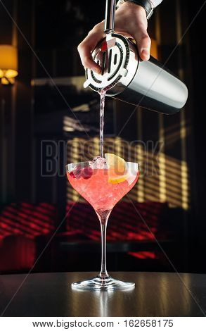 Barman at work, preparing cocktails. pouring margarita to cocktail glass. concept about service and beverages.
