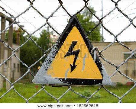 high-voltage wires a sign on the fence the danger