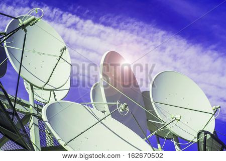 Satellite dish on blue sky background .