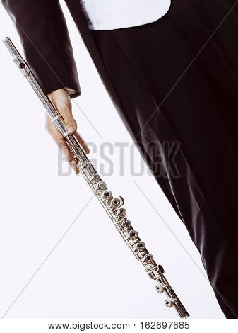 Classical music study concept. Male flutist musician performer with flute. Young elegant man wearing tailcoat holds instrument part of body