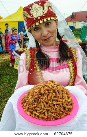Tyumen, Russia - June 24, 2016: The 5th open championship of Russia on a plowed land. Woman in national costumes with national food at center of Tatar culture