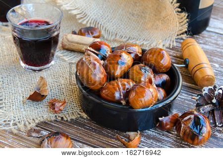 Delicious roasted chestnuts on ceramic bowl and glass of red wine on old wooden table bottle of wine fir cone cork and vintage corkscrew in the background.