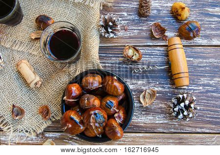 Delicious roasted chestnuts on ceramic bowl and glass of red wine on old wooden table bottle of wine fir cone cork and vintage corkscrew in the background. Top view. Flat lay.